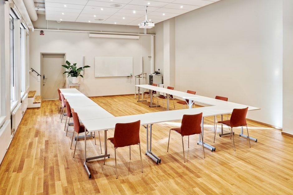 Ett rum med whiteboardtavla och bord som står i en halv fyrkant med tillhörande stolar